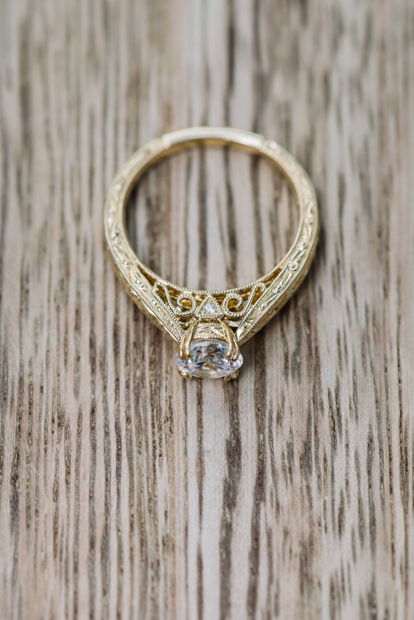 Yellow gold engagement ring by Kirk Kara with hand engraving and a single round diamond on a wood grain background
