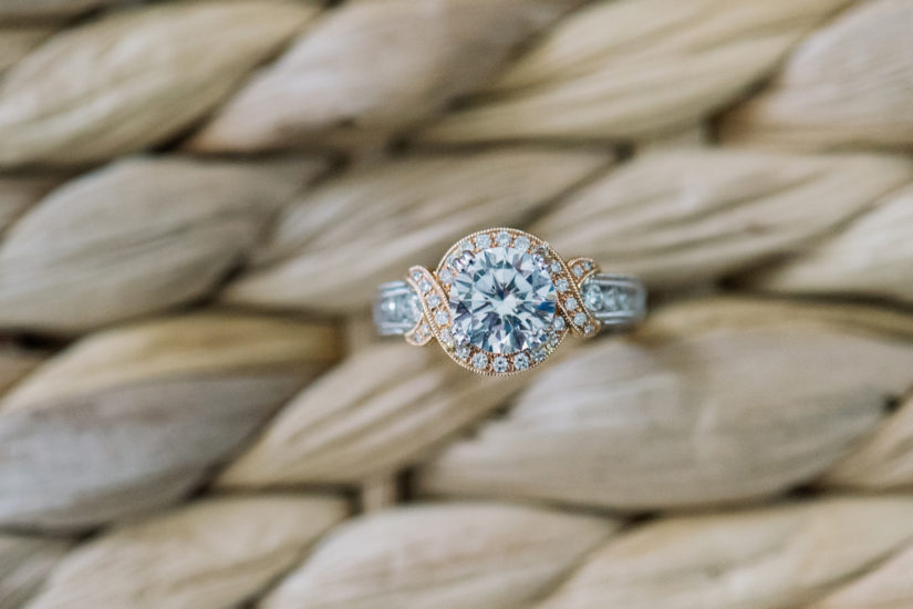 Two toned gold engagement ring with large round halo center on a woven grass background
