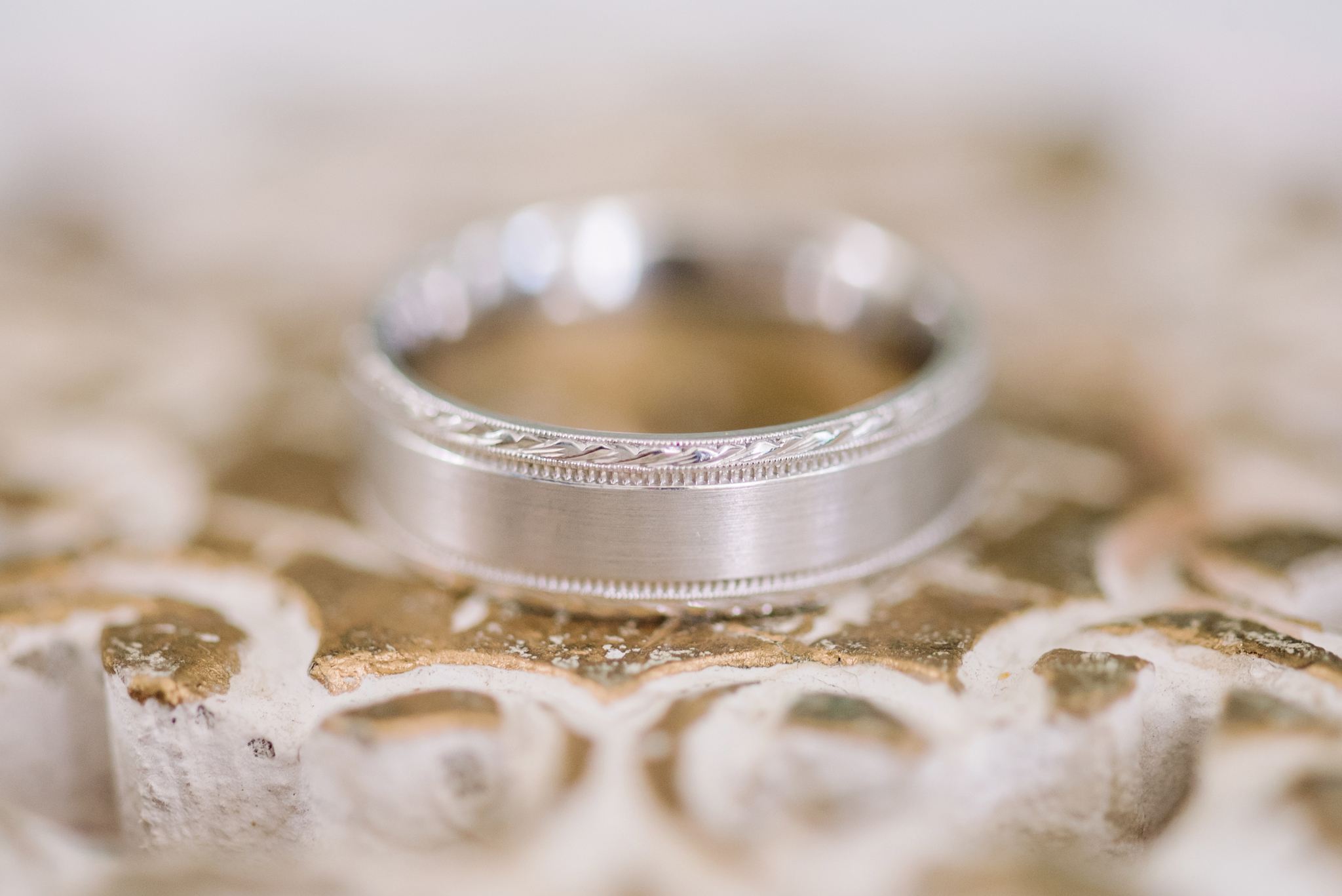 Men's wedding band in white gold on a swirling rose gold background