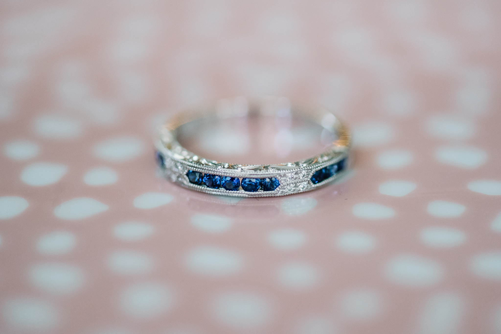 Wedding band with blue colored sapphires in white gold on a pink polkadot background