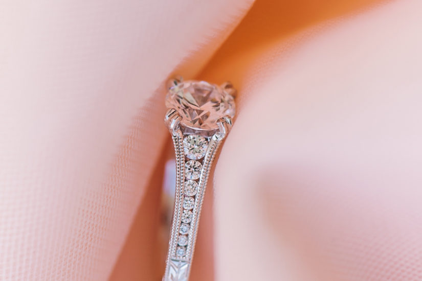 White gold and diamond engagement ring on a soft pink fabric background