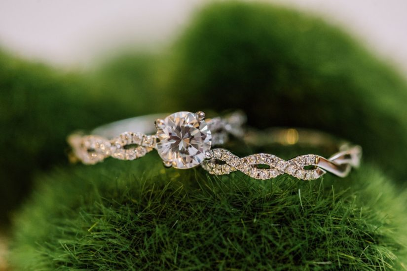 Matching diamond and white gold engagement and wedding ring set on green moss