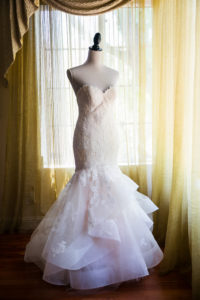 Wedding dress on a stand with golden curtains in the background