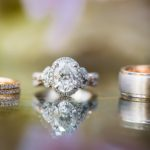 Beautiful set of Kirk Kara engagement and wedding rings on a reflective background