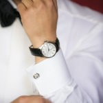 Man adjusting cufflinks while getting ready for a wedding wearing a fine watch and a white shirt