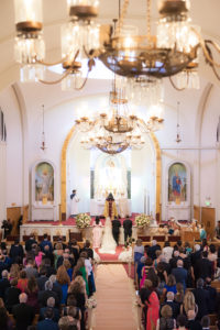 Looking down the isle of a traditional Armenian wedding ceremony with chandeliers hanging overhead