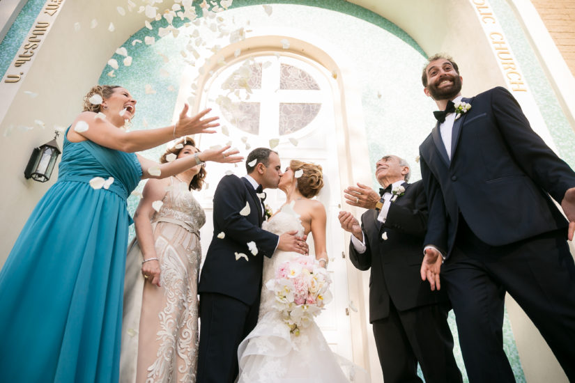 Throwing flower petals in the air while the bride and groom kiss during their wedding