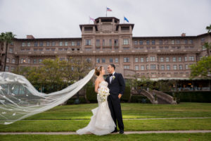 Bride and Groom on a field of grass with a grand old brick building in the background