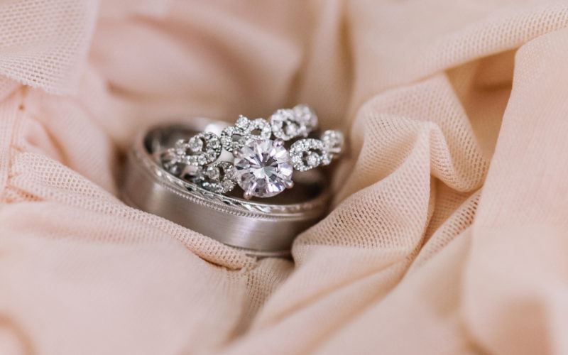 Set of platinum and diamond rings on a soft peach fabric