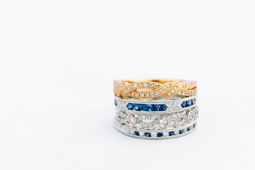 Stack of Kirk Kara yellow and white gold wedding bands, some with sapphires, on a white background