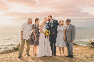 Sun setting on the beach in Hawaii with bride and groom and family