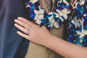 Kirk Kara engagement and wedding rings with blue lei at Hawaiian Wedding