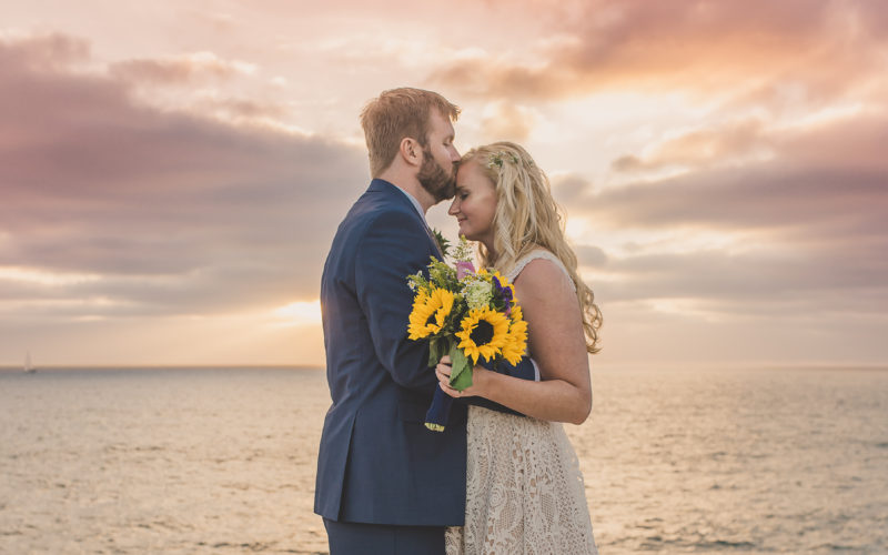 Couple kissing during wedding photoshoot during sunset with sunflowers and Kirk Kara rings