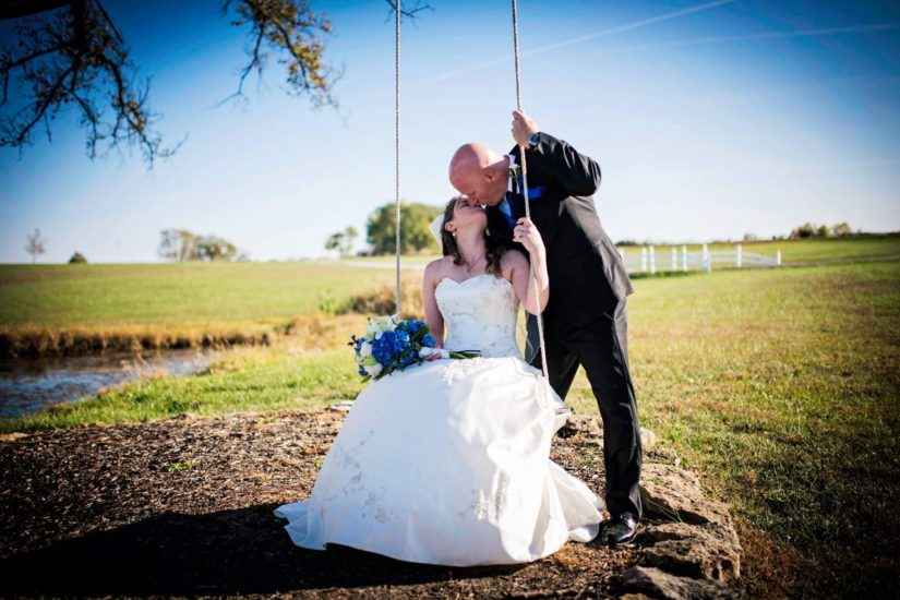 Photoshoot of couple kissing in a field
