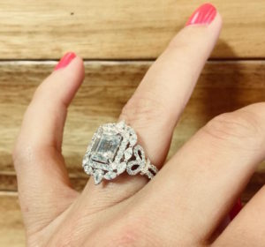 Large custom white gold and diamond engagement ring on hand with wood background.