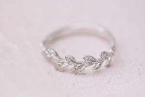 White gold engagement ring with leaves on a pink background