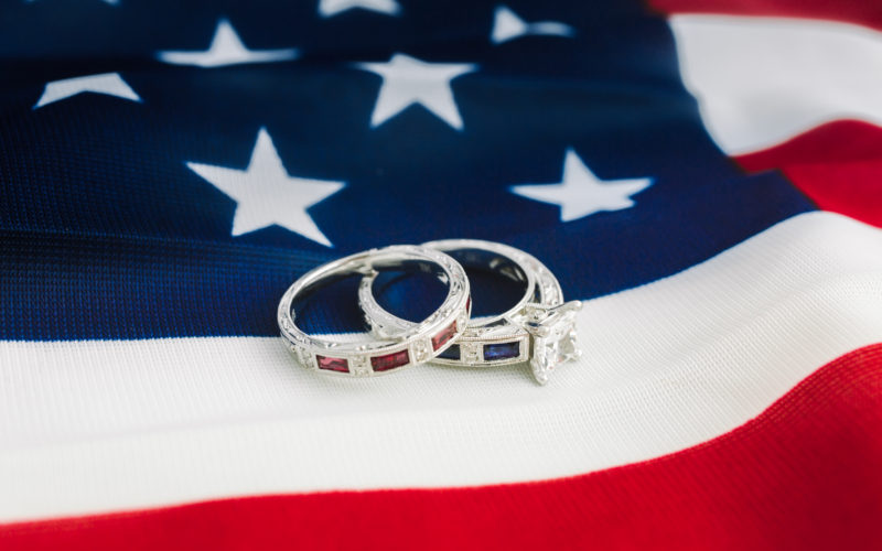 White gold engagement ring with sapphires and diamonds with white gold wedding band with rubies on American flag