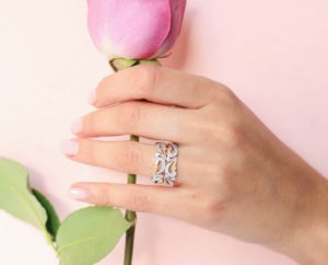 Swirling white, yellow and rose gold band on a hand holding a rose